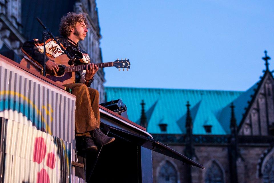 Mann mit Gitarre sitzt erhöht und schaut verträumt in die Ferne