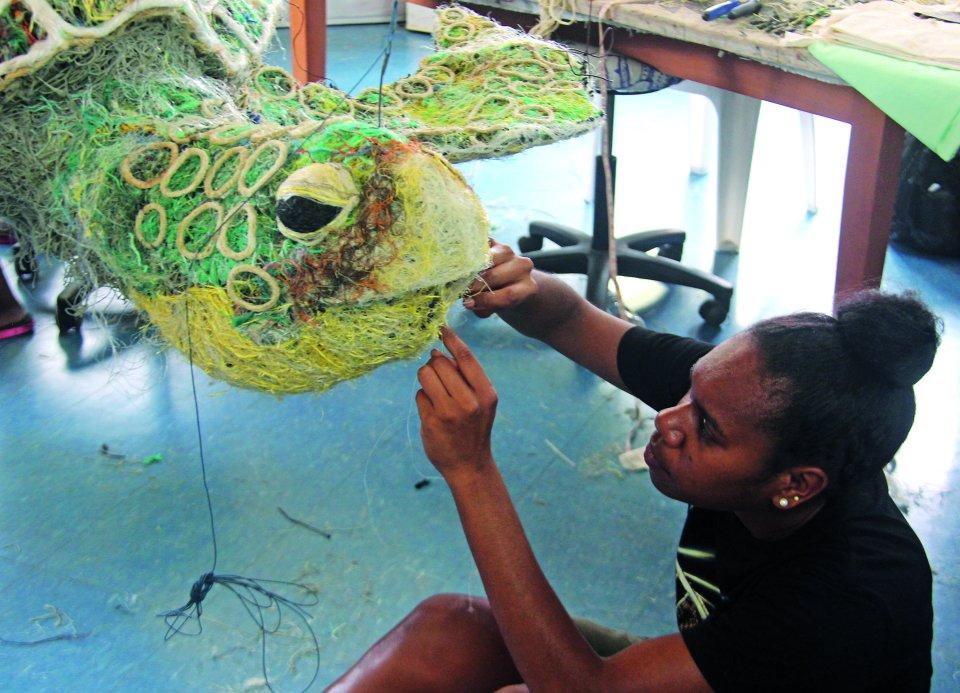 Mädchen arbeitet an einer Ausfertigung einer Schildkröte aus Fischernetzen