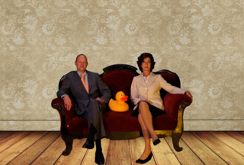 Zwei Schauspieler des Theaterschiffs Bremen sitzen mit einer großen Quietscheente auf einem Sofa.