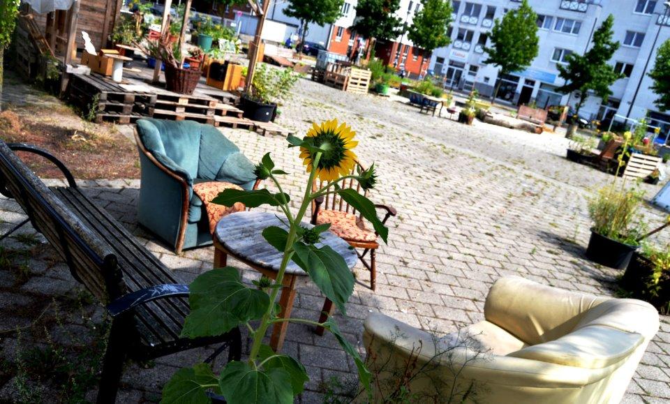Sitzgruppe mit Sesseln und einer Bank im urbanen Garten 'Lucie' in der Neustadt