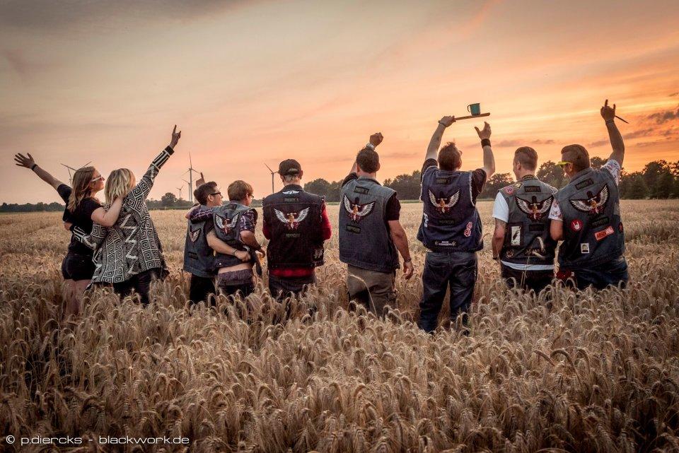 Eine Gruppe von Menschen steht im Feld und schaut den Sonnenaufgang an