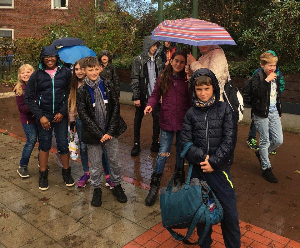 Kinder laufen durch den Regen.