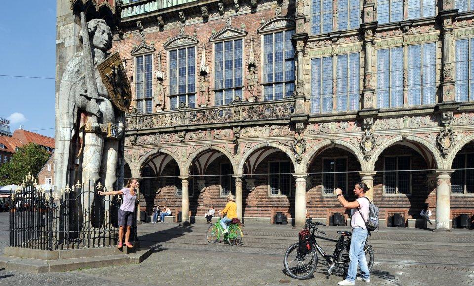 Touristen machen Fotos am Roland auf dem Marktplatz.