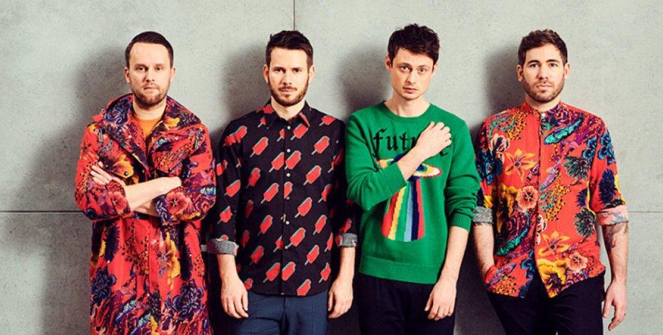 Die vier Bandmitglieder stehen in bunten Klamotten vor einer grauen Wand und blicken ernst in die Kamera.