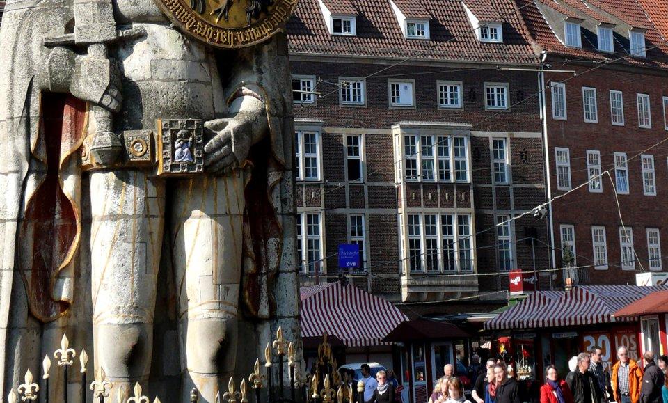 Am linken Bildrand die Kniespitzen des Rolands, auf der anderen Seite Passanten.