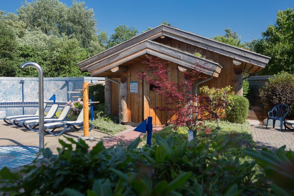 Außengelände einer Saunalandschaft mit Dusche und Holzsauna