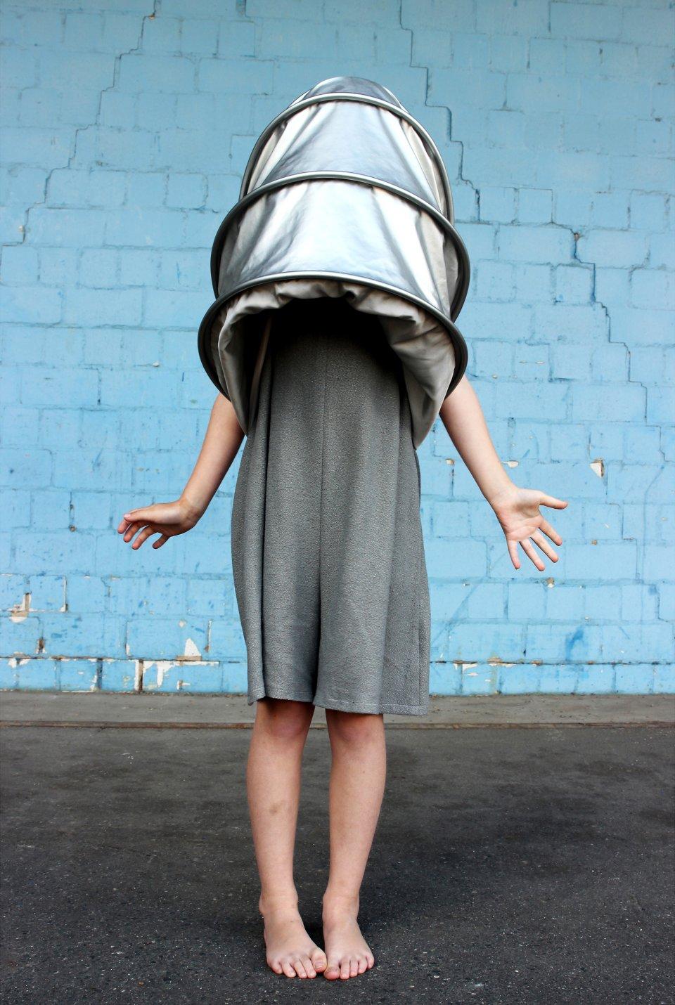 Ein kunstvoll verkleidetes Kind steht vor einer blauen Wand.