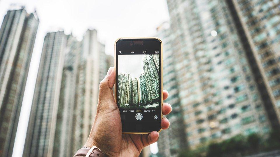 Eine Männerhand hält ein Smartphone auf Hochhäuser gerichtet. Die Kamera ist aktiviert.