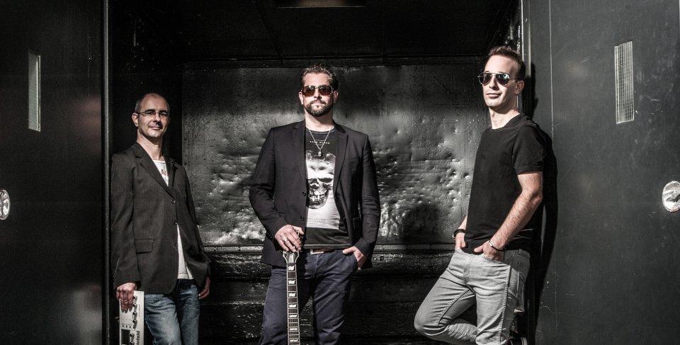 3 Männer stehen in einem dunklen Raum mit schweren Türen. Sie tragen Sonnenbrillen und haben ihre Instrumente vor sich.