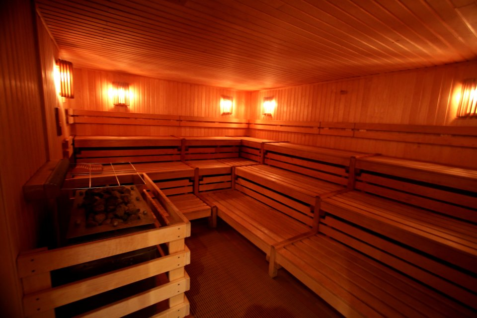 Blick in eine Sauna mit Sitzflächen aus Holz.