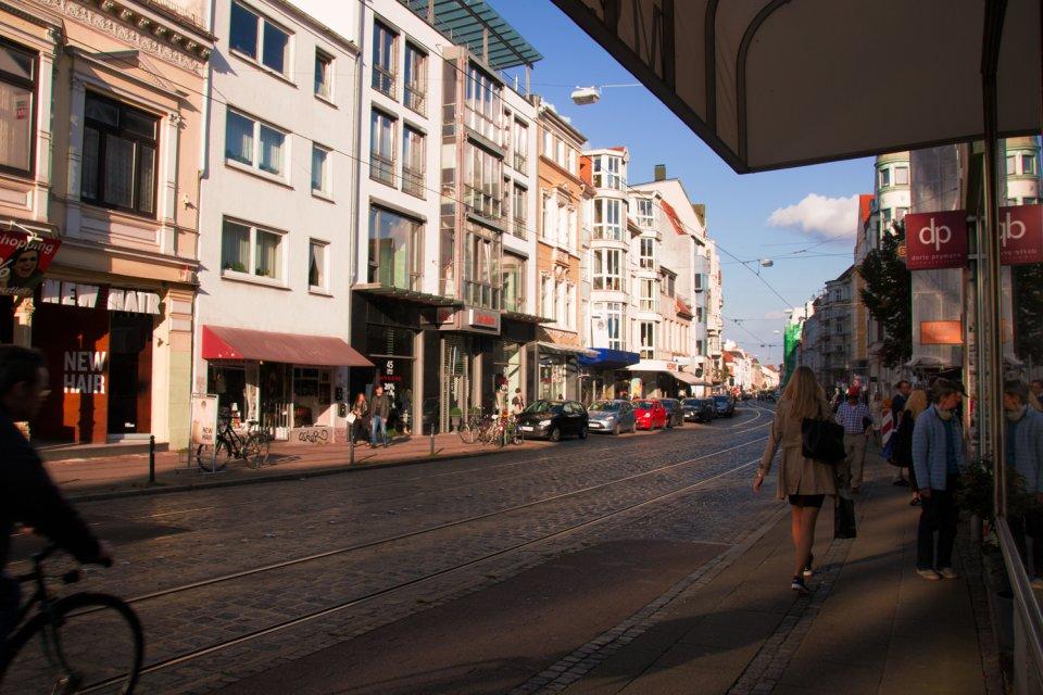 Ostertorsteinweg in der Abensonne, Menschen blicken in ein Schaufenster