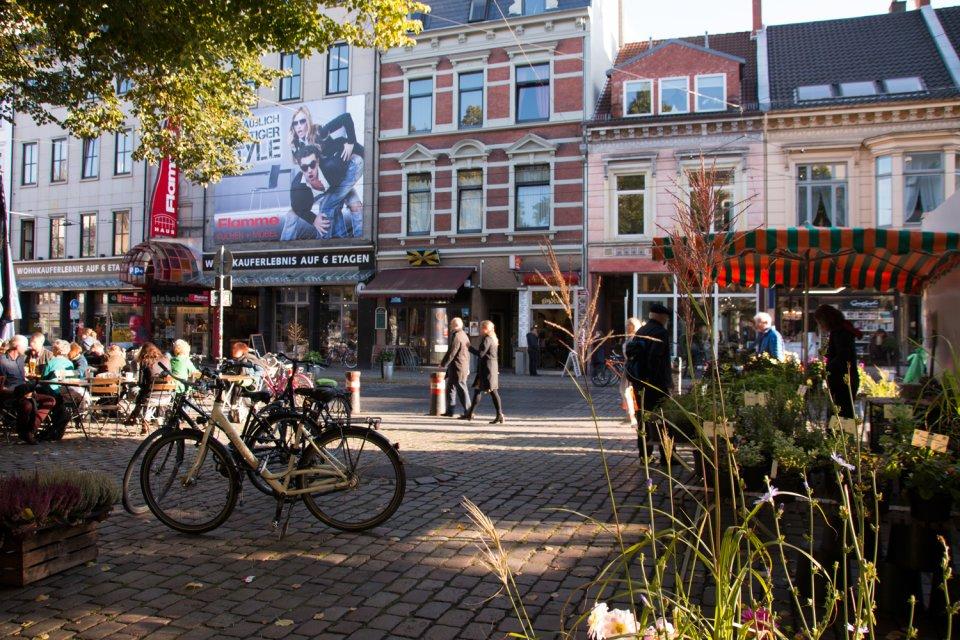 Blumenstand auf einem Platz im Viertel; Menschen genießen die Abendsonne im Café