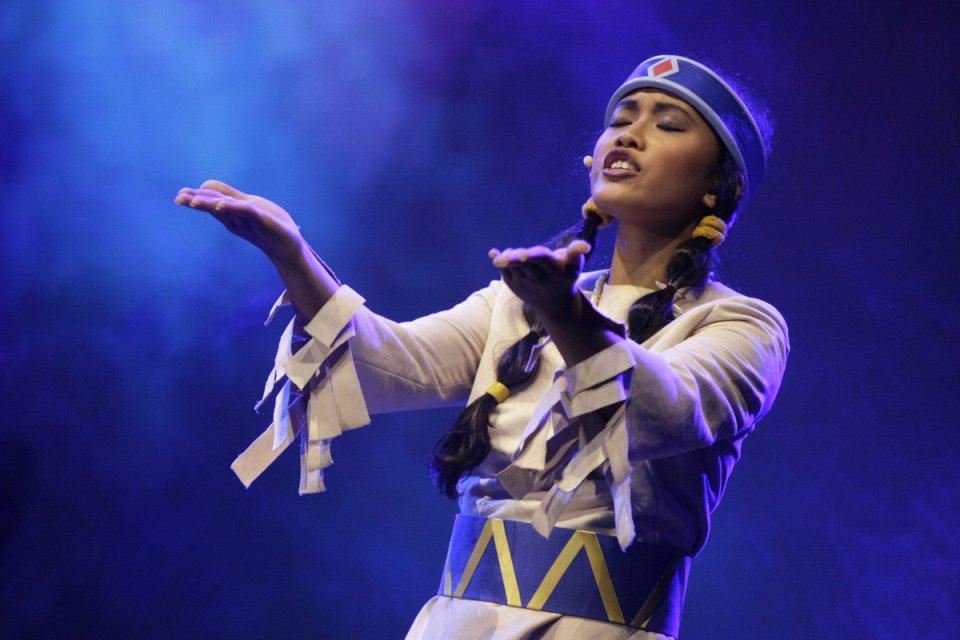 Ein Mädchen ist als Indianerin verkleidet und singt auf der Bühne.