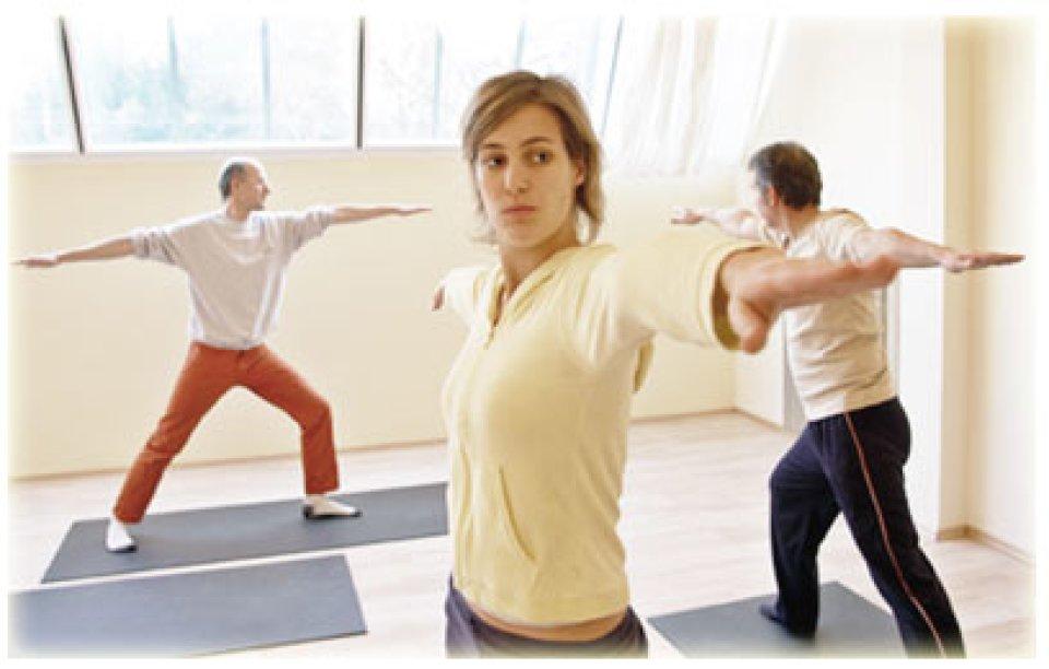 3 Menschen stehen auf Matten und machen Yoga.